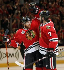 Chicago Blackhawks defenseman Brent Seabrook, right, is congratulated by defenseman Brian Campbell after a goal in the first period of Game 5 of the NHL Stanley Cup Final.