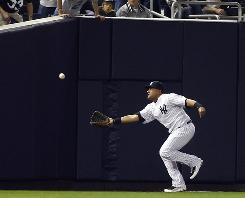 The Yankees' Melky Cabrera is unable to catch a ball in fair territory during last year's playoffs which was called foul.