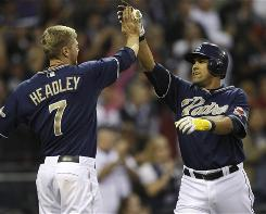 Oscar Salazar, right, gets a high-five from teammate Chase Headley after Salazar's three-run pinch-hit home run in the eighth inning.