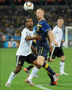 Australia's Craig Moore, battling Germany's Cacau, left, for the ball during their World Cup game Saturday, was diagnosed with testicular cancer in late 2008.