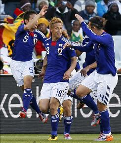 Japan's Keisuke Honda, center, celebrates with teammates Yuto Nagatomo, left, and Marcus Tulio Tanaka after scoring during the World Cup Group E against Cameroon. Japan won 1-0, their first World Cup victory outside of Asia.