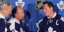 Newly announced Toronto Maple Leafs captain Dion Phaneuf, right, is congratulated by former Maple Leafs captains Darryl Sittler, left, and Wendel Clark during a news conference in Toronto.