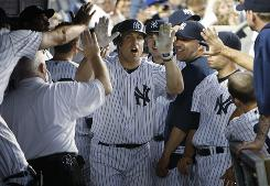 The Yankees' Mark Teixeira, center, is congratulated on his solo home run during the fifth inning against the Philadelphia Phillies at Yankee Stadium.