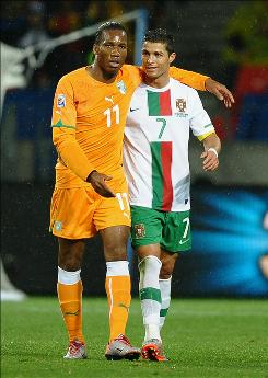 Didier Drogba of Ivory Coast, who came on as a substitute in the 66th minute, puts his arm around Cristiano Ronaldo of Portugal during the teams' 0-0 draw in Group G play.