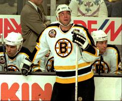 Former Bruins star Cam Neely, front, checks the scoreboard during a 1996 game against the Hartford Whalers.