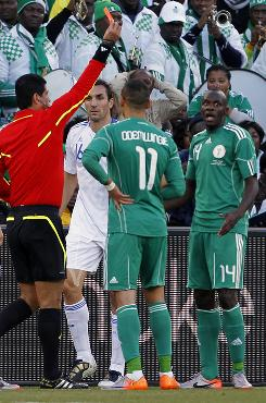 Nigeria's Sani Kaita, right, expresses surprise after getting a red card from referee Oscar Ruiz, red shirt, against Greece.