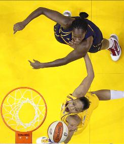 Los Angeles Sparks' Tina Thompson, below, puts up a shot as Connecticut Sun's Tina Charles defends during the first half in Los Angeles. Charles led Connecticut with 26 points and a career-high 19 boards.