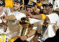 Los Angeles Lakers guard Derek Fisher, center, holds the Larry O'Brien Trophy as Kobe Bryant, right, holds the MVP trophy as they celebrate after beating the Boston Celtics, 83-79, in Game 7 of the NBA Finals. The team will hold a victory celebration in Los Angeles Monday.