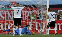 Serbia goalkeeper Vladimir Stojkovic saves the penalty kick of Germany's Lukas Podolski, right.