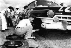 Raymond Parks changes a tire on his race car driven by Red Byron during the first Southern 500 in 1950.