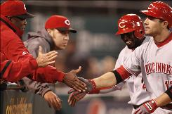 Reds manager Dusty Baker, front left, congratulates Joey Votto, front right, after Votto hit a two-run homer to drive in Brandon Phillips, back right, who singled in the 10th inning.