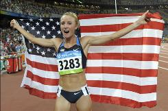 Shalane Flanagan celebrates with the U.S. flag after winning the bronze medal in the women's 10,000-meter final during the athletics competitions in the National Stadium at the Beijing 2008 Olympics.