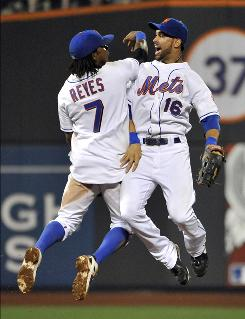 The Mets' Jose Reyes and Angel Pagan celebrate after the 14-6 win over the Tigers. The pair combined for seven of New York's 16 hits.