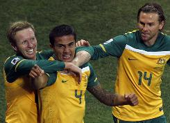 Australia's Tim Cahill, center, celebrates his goal against Serbia with teammates Brett Holman, right, and David Carney. Holman added a goal four minutes later but the Socceroos still fell short.