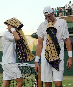 Nicolas Mahut, left, of France and John Isner of the USA look weary as their epic five-setter continues at Wimbledon.