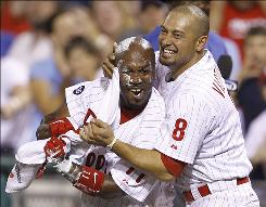 Jimmy Rollins, left, gets a shaving cream towel to the face from teammate Shane Victorino after Rollins hit a walkoff, two-run homer in the bottom of the ninth to lead the Phillies to a 7-6 win over the Indians.