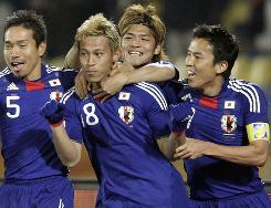 Japan teammates mob Keisuke Honda, second from left, after his free-kick goal opened the scoring against Denmark. Yusuhito Endo scored a free kick of his own and Honda assisted Shinji Okazaki on another goal as the Japanese took second place in Group E.