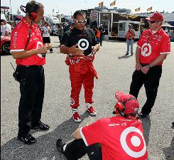 Juan Pablo Montoya talks with his crew after locking down the pole position at New Hampshire Motor Speedway.