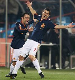 Spain's David Villa, right, celebrates his goal against Chile with Xavi Hernandez. Villa scored from 45 yards out after taking advantage of a poor decision by Chile goalkeeper Claudio Bravo.