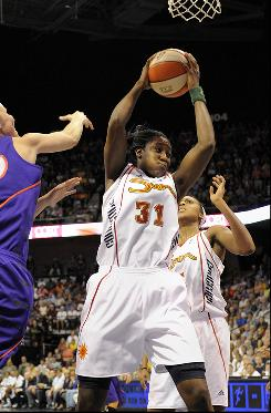 Connecticut center Tina Charles grabs one of her 23 rebounds. Charles set a franchise record for rebounds to help the Sun defeat the Phoenix Mercury.