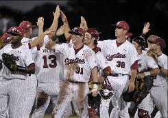 South Carolina players celebrate their 4-3 win over Clemson in an NCAA College World Series baseball elimination game, in Omaha, Nebraska.