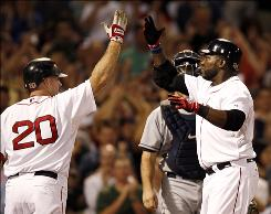 Boston's David Ortiz, left, is greeted at home by teammate Kevin Youkilis after Ortiz hit a three-run homer run during the fifth inning.