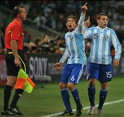 Argentina defender Gabriel Heinze, center pleads with a referee to watch the replay on the big screen after a disputed call during the World Cup Round of 16 match between Argentina and Mexico.