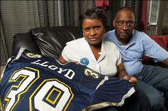 Bridgette and Dale Lloyd show the Rice University jersey of their son, Dale Lloyd II, who died in 2006, a day after collapsing following a workout. The Lloyds' lawsuit spurred the NCAA to test all athletes for the sickle cell trait, starting in August.
