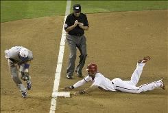Arizona's Chris Young steals third base as the Dodgers' Casey Blake fields the late throw while umpire Bill Hohn looks on in the third inning. Young propelled the Diamondbacks to a 12-5 win with a career-high five RBI.