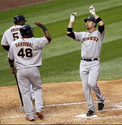 San Francisco's Travis Ishikawa, right, receives congratulations from teammate Pablo Sandoval after Ishikawa's first career grand slam.