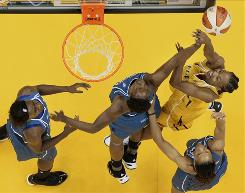 Tulsa's Chante Black, yellow jersey, shoots in front of three Washington defenders. The Mystics' defense held the Shock to just four points in the pivotal second quarter, and Washington won 69-54.