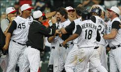The Rockies' Todd Helton, center, is congratulated by teammates after hitting a sacrifice fly to drive in the winning run in the 15th inning to beat the Giants 4-3.