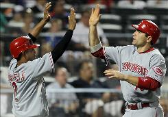 Reds teammates Orlando Cabrera and Joey Votto celebrate after scoring on a Drew Stubbs single in the fifth inning.