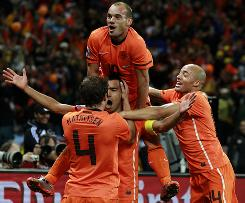 The Netherlands' Giovanni van Bronckhorst, center, celebrates his opening goal against Uruguay with teammates Wesley Sneijder, top, Demy de Zeeuw, right, and Joris Mathijsen. Sneijder scored later in the game and Arjen Robben added a third as the Dutch edged the South Americans to return to the World Cup final for the first time since 1978.