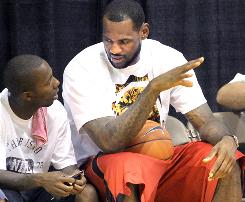 LeBron James, right, talks with business partner Rich Paul during an afternoon workout at his basketball camp in Akron.