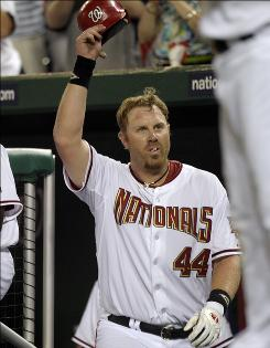The Nationals' Adam Dunn takes a curtain call and tips his hat after hitting his third home run against the Padres during the eighth inning.