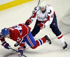 Washington Capitals defenseman Jeff Schultz, checking the Montreal Canadiens' Dominic Moore during the playoffs, led the league in plus-minus (plus 50) during the regular season.
