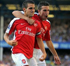 Dutch striker Robin van Persie puts his arm around Spainish midfielder and Arsenal teammate Cesc Fabregas during an English Premier League match last August. The two club teammates will be opponents when Spain takes on the Netherlands in the World Cup final this Sunday.