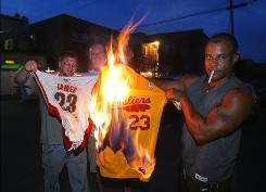 Upset with the most recent of Cleveland sports tragedies, Cavaliers fans, from left, Josh Hall, Rob Hose, and Mike Adams set fire to LeBron James jerseys.