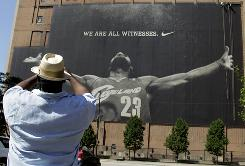 Leonard Ramsey photographs workmen removing the large mural of LeBron James rom a building in downtown Cleveland.