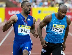 Tyson Gay, left, and runner-up Asafa Powell pull up after crossing the finish line in their 100-meter showdown in Gateshead, England.