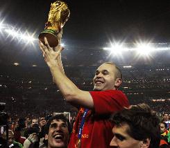 Spain's Andres Iniesta lifts the World Cup trophy after beating the Netherlands in extra time in Johannesburg. Iniesta scored the game's only goal in the 116th minute of play to give Spain its first World Cup title.