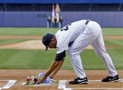 Yankees closer Mariano Rivera lays two roses across home plate during a tribute to New York owner George Steinbrenner, who died Tuesday, before the team's game against the Tampa Bay Rays on Friday.