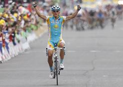 Alexandre Vinokourov of Kazakhstan keeps the pack behind him as he crosses the finish line to win the 13th stage of the Tour de France.