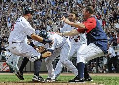 Twins' Michael Cuddyer, left, is greeted by Nick Punto, J.J. Hardy and Jim Thome, right, after he scored the winning run on a Delmon Young hit off White Sox pitcher Dergio Santos in the ninth inning.