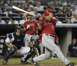 Angels designated hitter and former Yankee Hideki Matsui follows through on two-run homer as New York catcher Jorge Posada watches during the seventh inning.