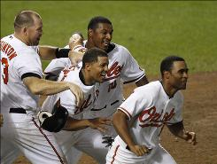 The Orioles' Cesar Izturis, center, celebrates with teammates Ty Wigginton, left, Adam Jones (10) and Corey Patterson, right, after he scored the winning run against the Rays in the 13th inning. Baltimore won 11-10.