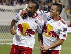 Thierry Henry celebrates with New York Red Bulls teammate Seth Stammler, right, after scoring a goal during the first half of an exhibition match against Tottenham.