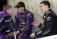 Carl Edwards, right, talks with Roush Fenway Racing teammate Matt Kenseth, center, and Jeff Burton during Friday practice for the Brickyard 400.