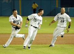 Marlins pinch hitter Donnie Murphy, center, celebrates with second baseman Dan Uggla, left, and catcher Ronny Paulino after driving in the winning run in the bottom of the ninth.